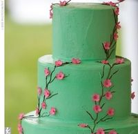 Elegant green buttercream cake with (edible!) pink cherry blossoms.