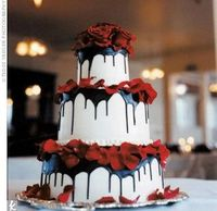 three-tier cake drizzled with chocolate ganache, then decorated with roses and rose petals. theknot.com