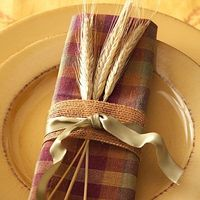 "Capture the spirit of the heartland with golden stalks of wheat. Fold a napkin in quarters, then thirds. Wrap a loose-weave ribbon, about 1¼"" wide, around the middle of the napkin and secure it in back with a glue dot. Layer a narrow wired ribbon on ..."