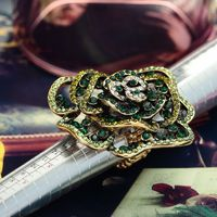 This antique flower ring features a large peony flower design paved with small round rhinestones.The peony big flower ring is crafted in gold plated alloy and offers a stretch band for a variety of finger sizes.