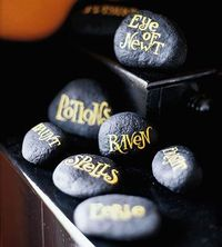 "Witching Words ""Sprinkle a handful of spellbinding stones on a tabletop to make guests stop and ponder. Use acrylic paints to blacken stones, then hand write or stencil seasonal words or phrases on the tops"""